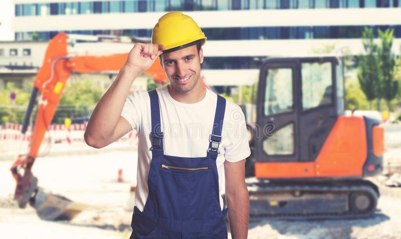 Red earthmover with handsome latin american construction worker royalty free stock images