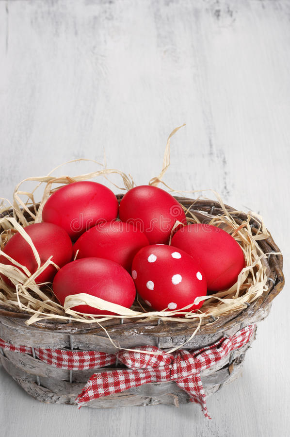 Red Easter eggs in basket royalty free stock images