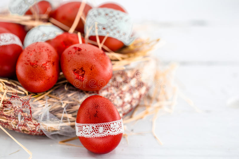Red Easter eggs in a nest of hay stock image
