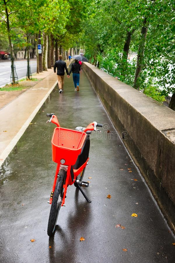 Red electric bicycle on side walk. During rainy day, ecological transportation royalty free stock photos