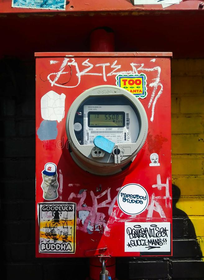Red Electric Meter on Urban Building Exterior Wall. stock photography