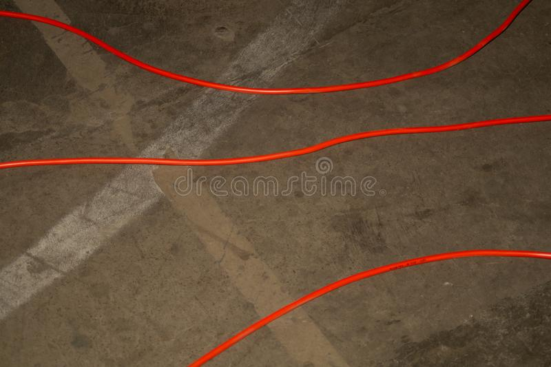 Red electric power cable. red wire lies on the ground. mess on cement floor. Industrial background, electrical, connection, electricity, energy, equipment stock images