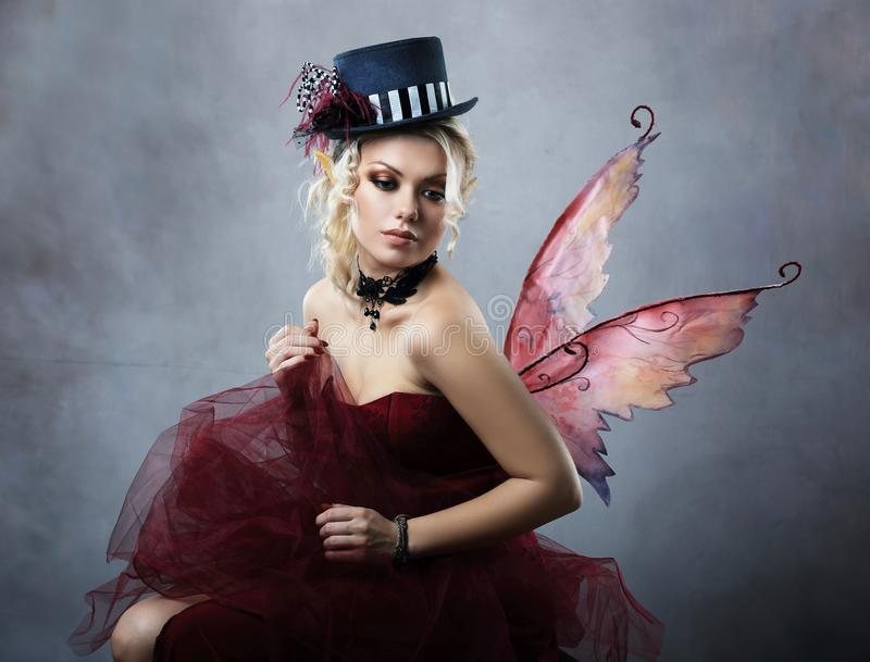Red elf fairy in fancy hat sitting. Red elf fairy wearing fansy hat over blue fantasy background stock images