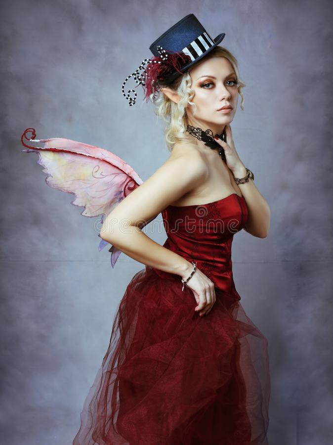 Red elf fairy in fancy hat. Red elf fairy wearing fansy hat over blue fantasy background royalty free stock photography