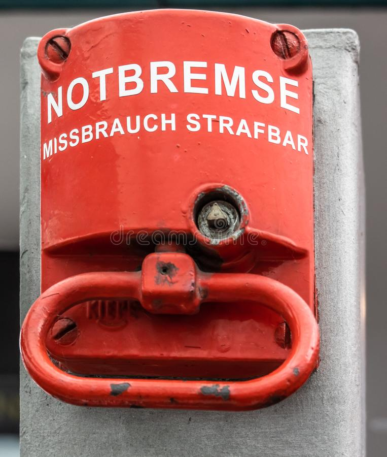 Red emergency brake to stop a large rolling staircase, with German inscription. `emergency brake, misuse punishable stock photos