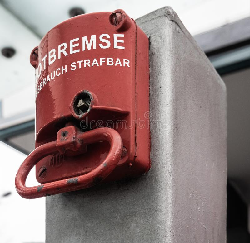 Red emergency brake to stop a large rolling staircase, with German inscription. `emergency brake, misuse punishable stock images