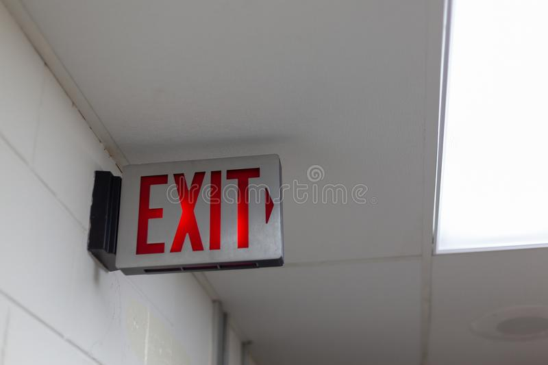 red emergency exit sign in the dark room. illuminated office exit sign stock images