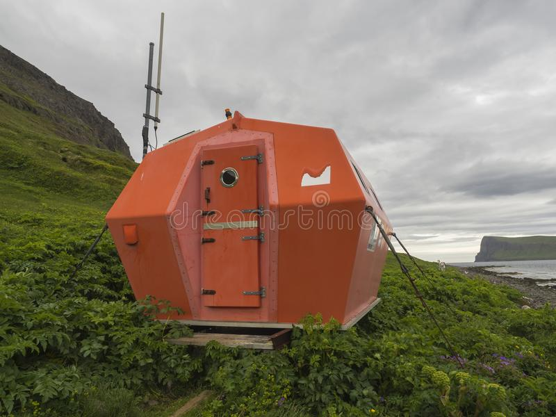 Red emergency shelter cabin in Hornvik standing on the sea shore grass meadow with view on hornbjarg cliffs stock image