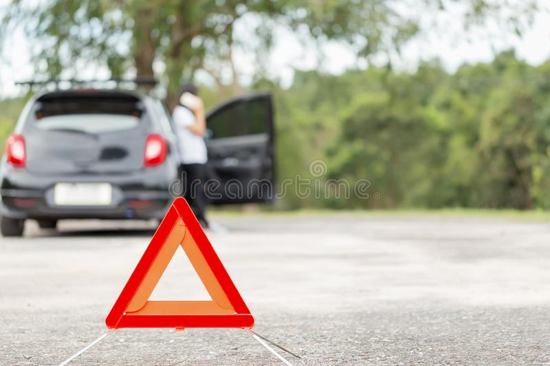 Red emergency stop sign with blurred car and woman calling car m. Echanic in the background royalty free stock images