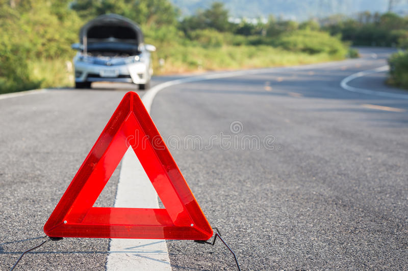 Red emergency stop sign and broken car on the road royalty free stock photos