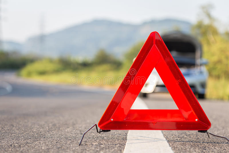 Red emergency stop sign and broken car on the road royalty free stock image