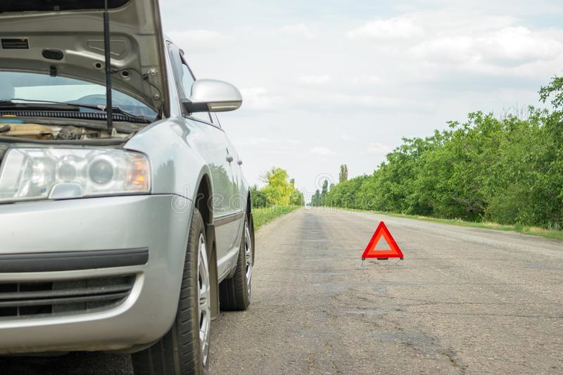 Red emergency stop sign and broken silver car on the road stock image