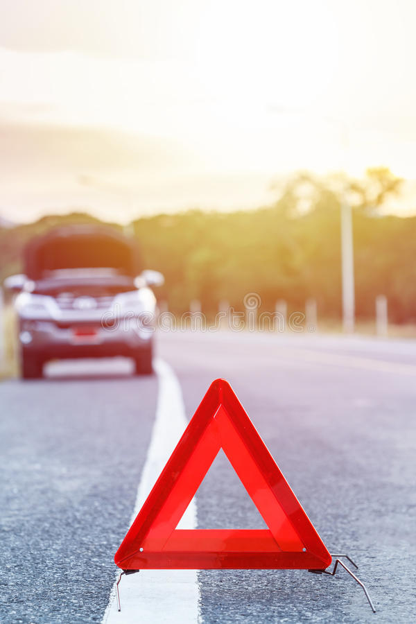 Red emergency stop sign and broken silver car on the road stock images