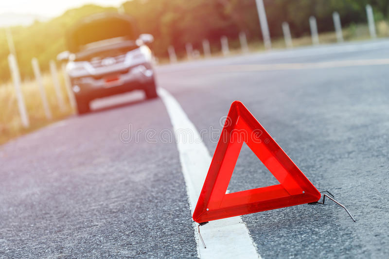 Red emergency stop sign and broken silver car on the road royalty free stock photos