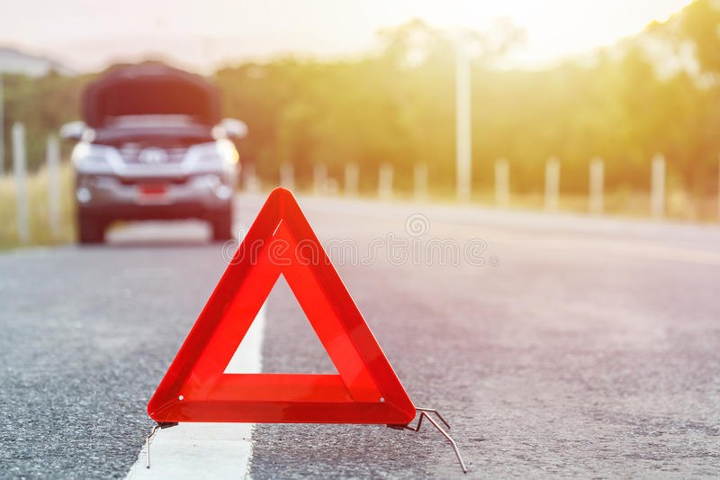 Red emergency stop sign and broken silver car on the road royalty free stock image