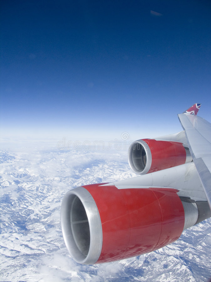 Red Engines. View from an aeroplane window of the red engines over some mountains with a deep blue sky stock photos
