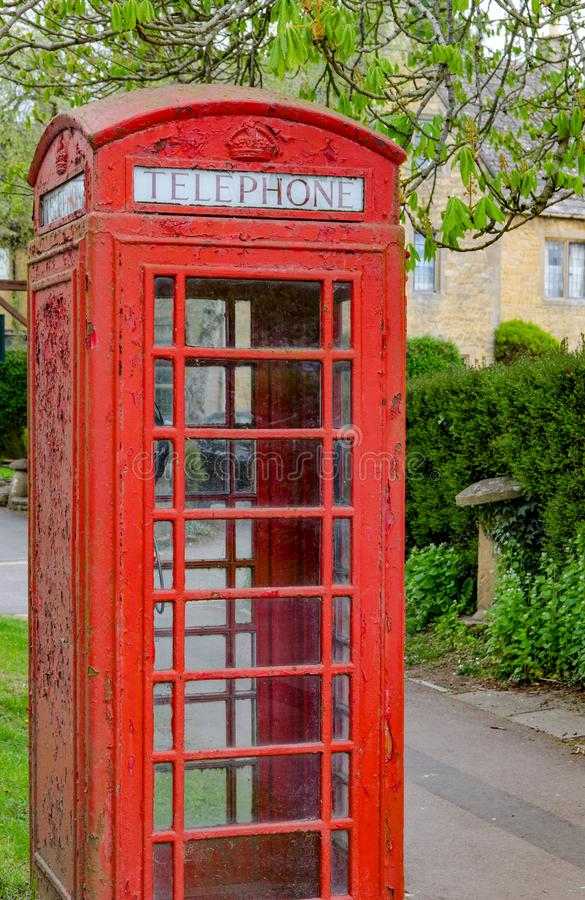 A red English phone box in a rural Cotswold village. This red British phone box is located in the Cotswold village of Bourton on the Water royalty free stock photography
