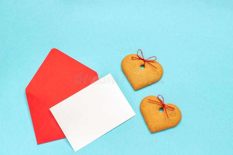 Red envelope with blank white card for text and heart shaped ginger cookies on blue background royalty free stock photography