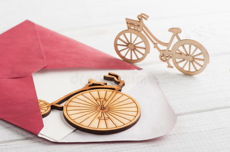 Red envelope with empty paper and wooden bikes. On white table. Travel concept royalty free stock image