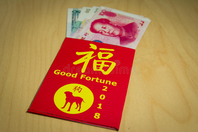 The red envelope or hong bao is used for giving money during Chinese New Year in China and Taiwan. 2018 is the dog`s year. Chinese words meaning Good fortune a royalty free stock photo