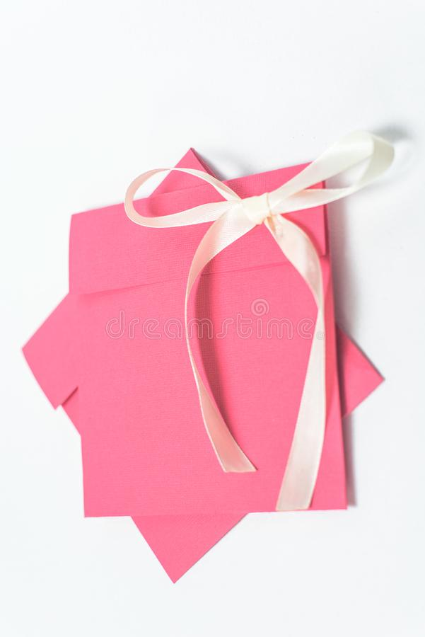 Red envelope with yellow ribbon in the shape of a bow for CD, vertical position . square envelope stock photography