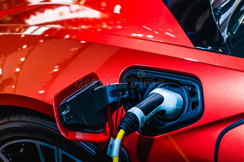 Red EV Car at charging station with the power cable supply plugged in. Power supply connect to electric vehicle for charging the royalty free stock photos