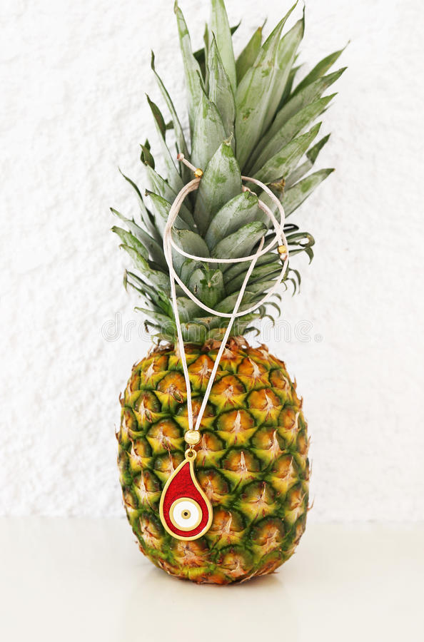 Red evil eye necklace advertisement on pineapple. Exotic fruit with greek jewelry royalty free stock images