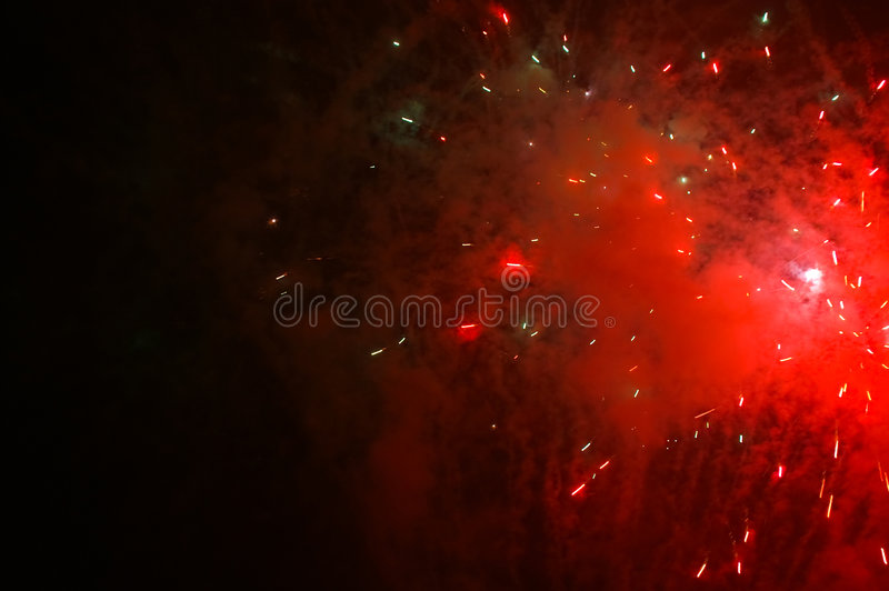 Red exploding fireworks on a dark sky royalty free stock photography