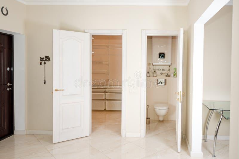red för hus för stolsdörringång inre modern Hänrycka hallet med vita dörrar till gå-i garderoben och toaletten arkivfoto