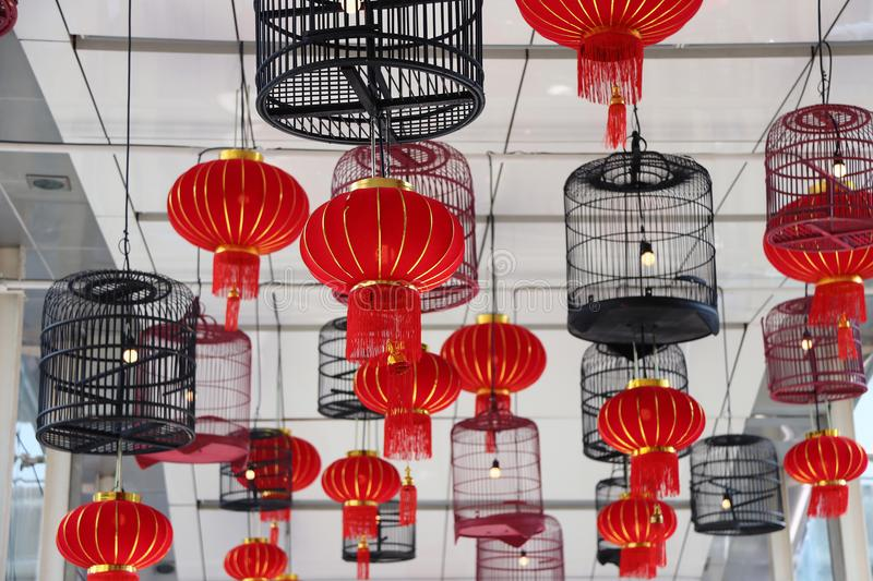Red fabric lamps and bird cage lamps hanging on the ceiling. stock image