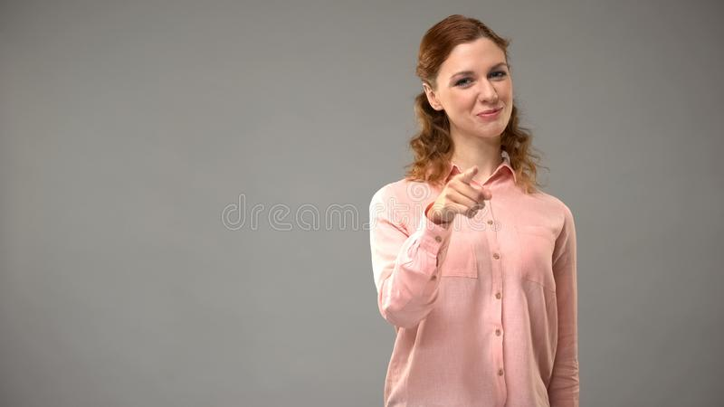 Red-faired lady pointing in camera on grey background, motivation tips, choice. Stock photo stock photography