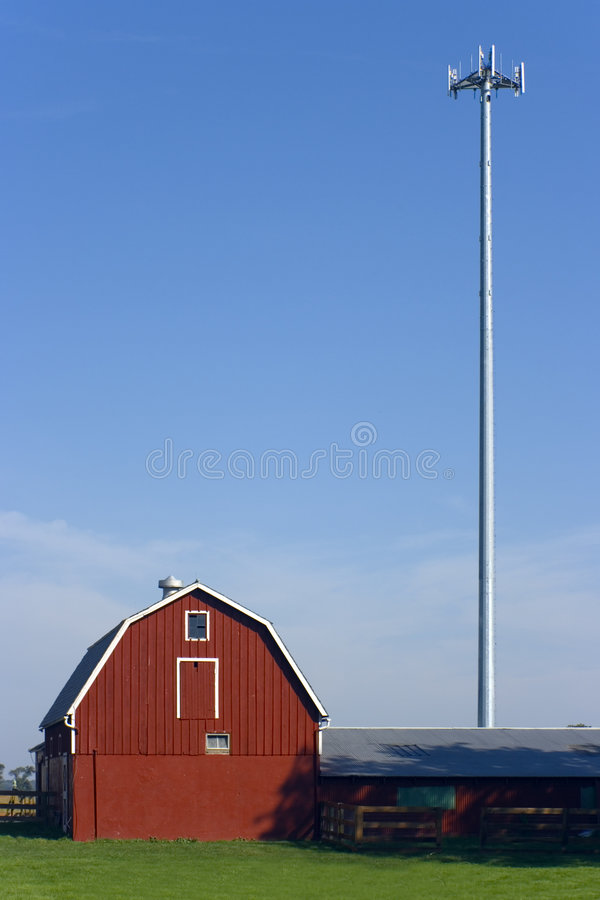 Red farm with a cell tower. stock photography