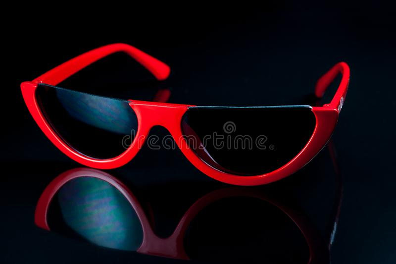 Red fashion sunglasses on a black background. Accessory, adult, attractive, autumn, beautiful, beauty, bright, city, clothes, color, cool, cute, face, female stock photo