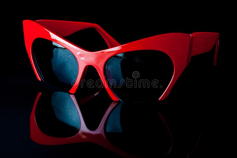 Red fashion sunglasses on a black background. Accessory, adult, attractive, autumn, beautiful, beauty, bright, city, clothes, color, cool, cute, face, female stock photos