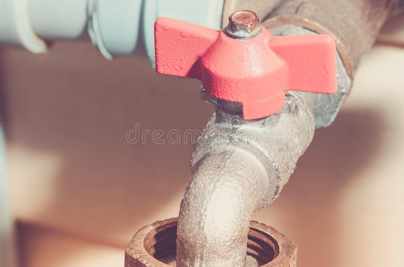 Red faucet and pipes/crane with the gate for water. Toned stock photo
