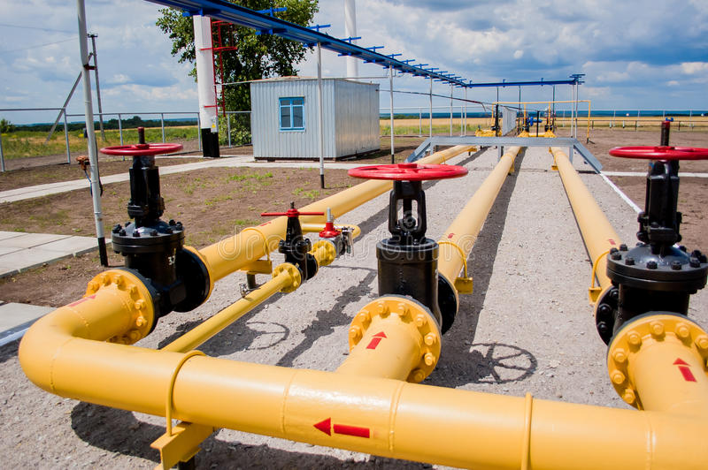 Red faucet with steel pipe in natural gas treatment plant. In bright sunny summer day stock image