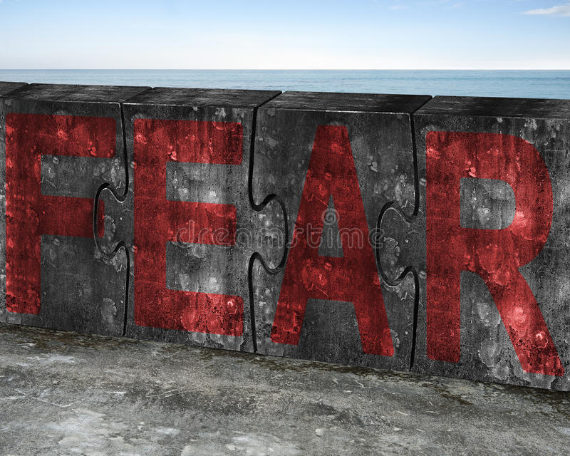 Red fear word on huge concrete puzzles with sea background. Red fear word on four huge concrete puzzles connected together, with sky sea background royalty free stock images