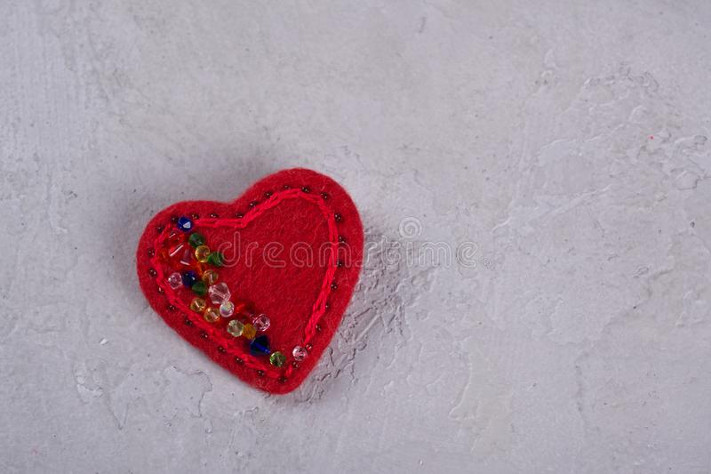 Red felt heart crafts decorated with beads on gray background . Valentines day decor stock image