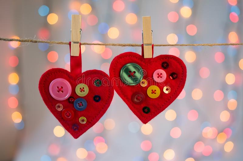 Red felt hearts crafts decorated with beads and buttons on colorful background with lights. Valentines day decor royalty free stock images