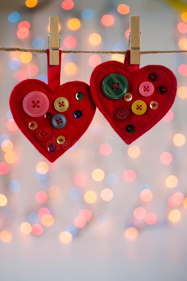 Red felt hearts crafts decorated with beads and buttons on colorful background with lights. Valentines day decor stock photo