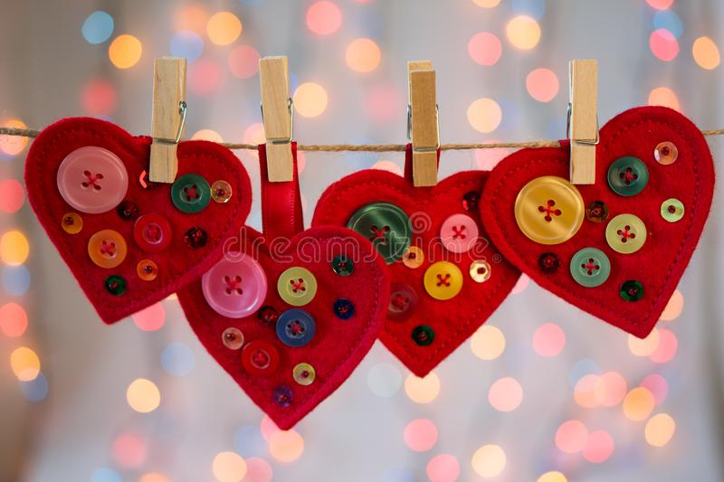 Red felt hearts crafts decorated with beads and buttons on colorful background with lights. Valentines day decor royalty free stock photos