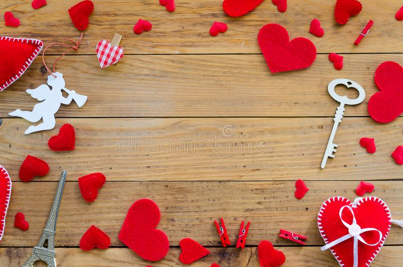 Red felt hearts and cupid angel border arrangement with copy space. Flat lay Happy Valentines day concept on wooden stock image