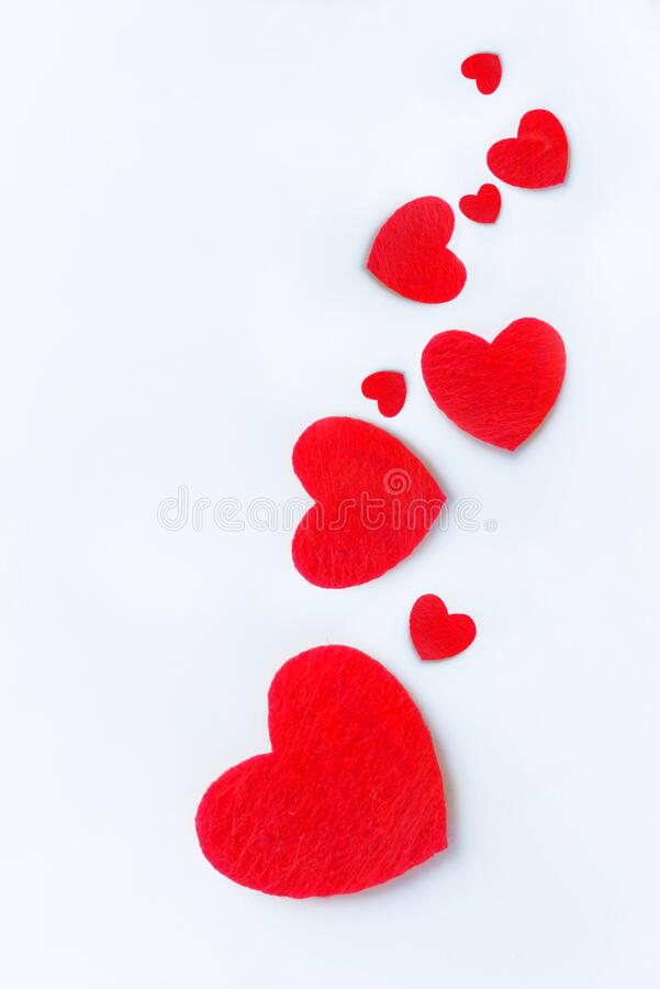 Red felt hearts on a white background. Valentine`s day symbol, holiday concept. Top view with copy space for text stock photo