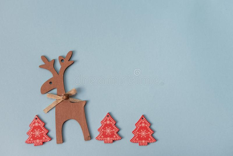 Red festive christmas hand made toys over the blue background with copy space for text and xmas decoration.Wooden deer royalty free stock photos
