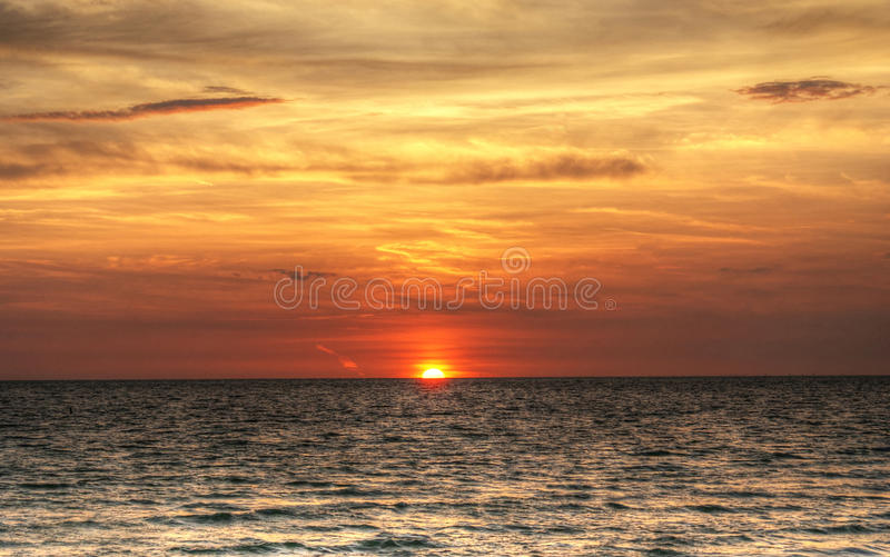 Red, fiery sunset over the ocean. With half of the sun`s disc, plumbeous water, brown clouds and golden sky royalty free stock photography