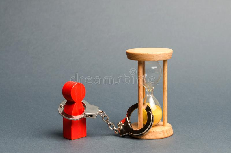 The red figure of a man is handcuffed to an hourglass. Dependence, there is little time left. Streamline business, increase royalty free stock images