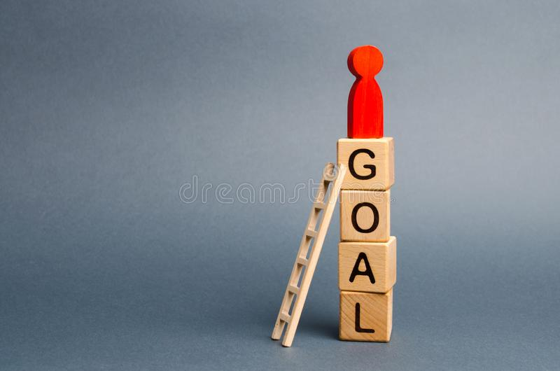 The red figure of a man stands on a tower of cubes with the word goal. Leadership skills. The concept of achieving the goal. Dedication and diligence stock photo