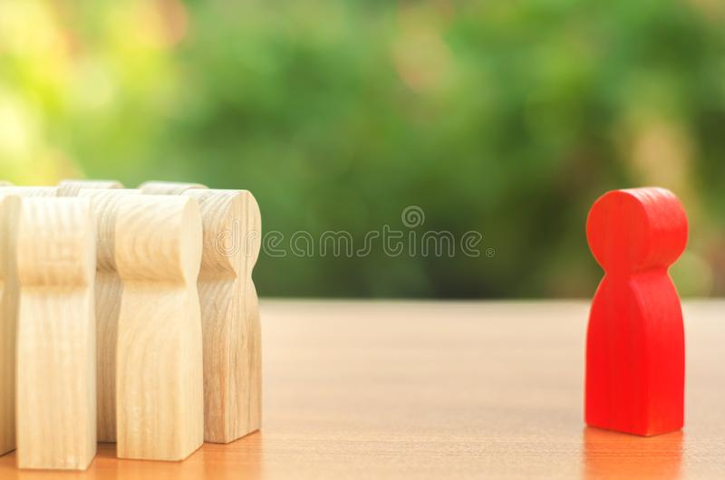 Red figurine of a man stands aside from the crowd of people. Asociality, sociopathy. Rejected from society, lonely. Infected, fear. Red figurine of a man stands stock image