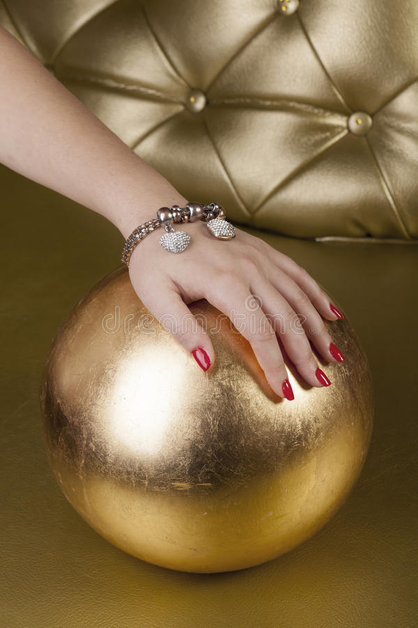 Red finger nails on a golden ball stock photography