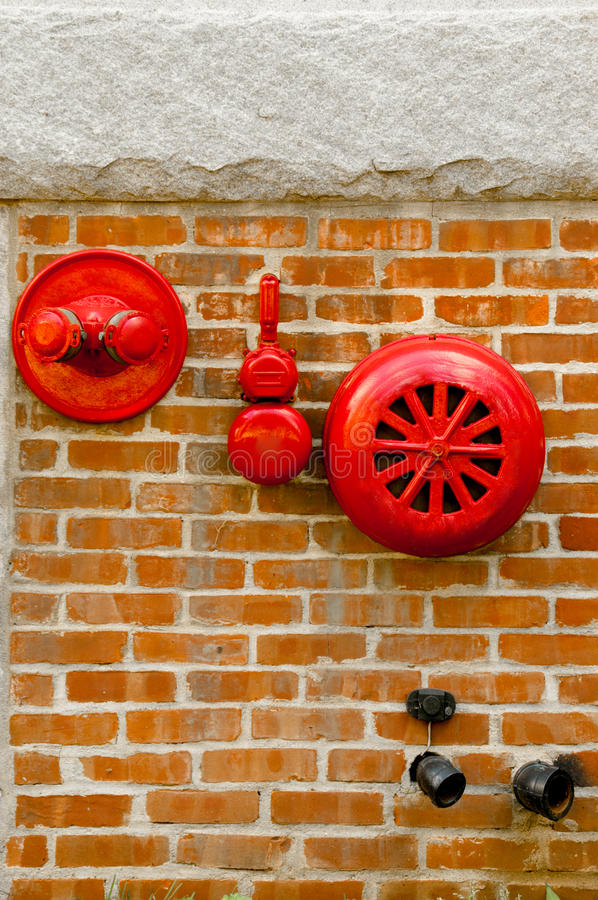 Red fire alarm sprinkler and hidrant in red brick wall.  stock photography
